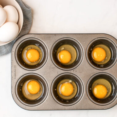 how to freeze eggs - 6 cracked eggs in a muffin tin, one egg per slot plus a bowl of eggs nearby