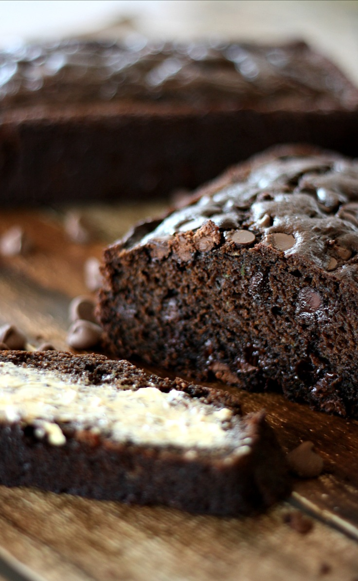 A loaf of chocolate bread cut with one slice buttered on the side.