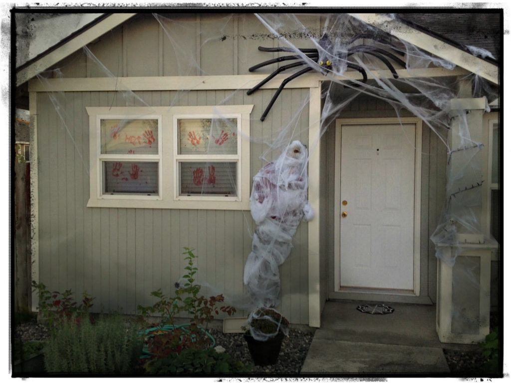 Thrifty & Super spooky halloween porch decorating idea using a spider and fake man. Creepy!