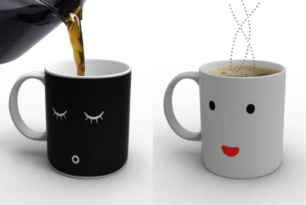 Two mugs - one black with sleeping eyes and one white wide awake