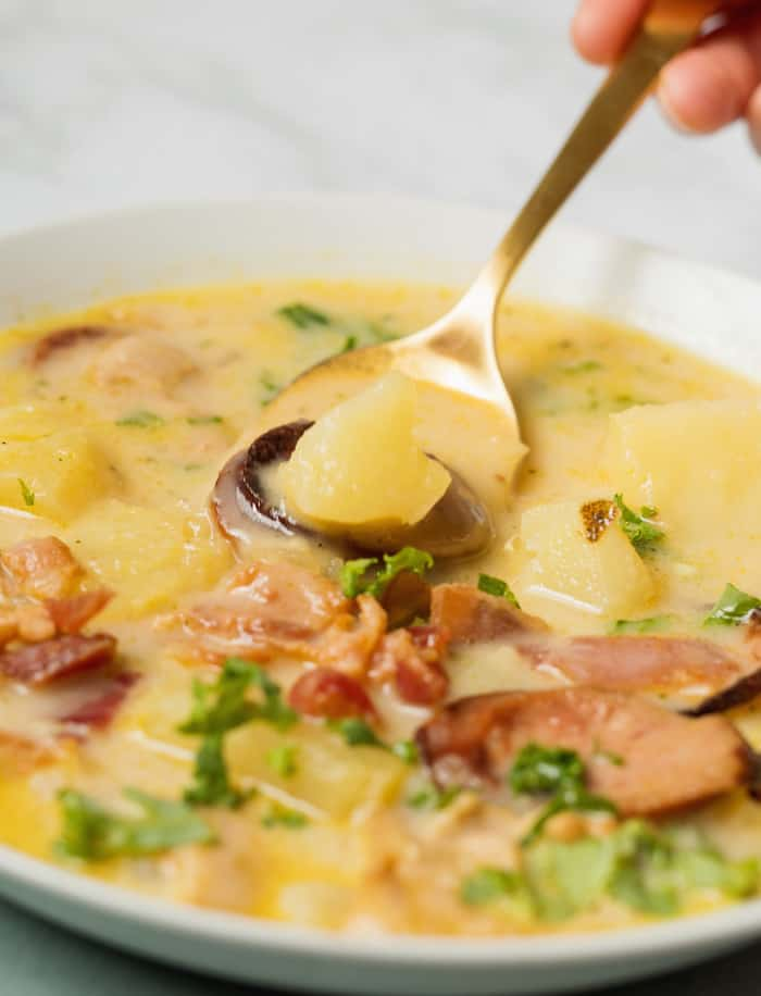 Zuppa Toscana soup in a white bowl with a spoon lifting out a bite with a potato on it.
