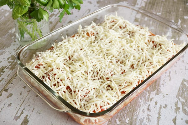 A glass pan with pasta covered in shredded cheese on it.