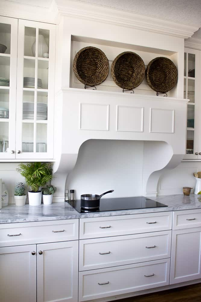 Gorgeous white kitchen with induction cooktop. Custom hood and white quartzite countertops.