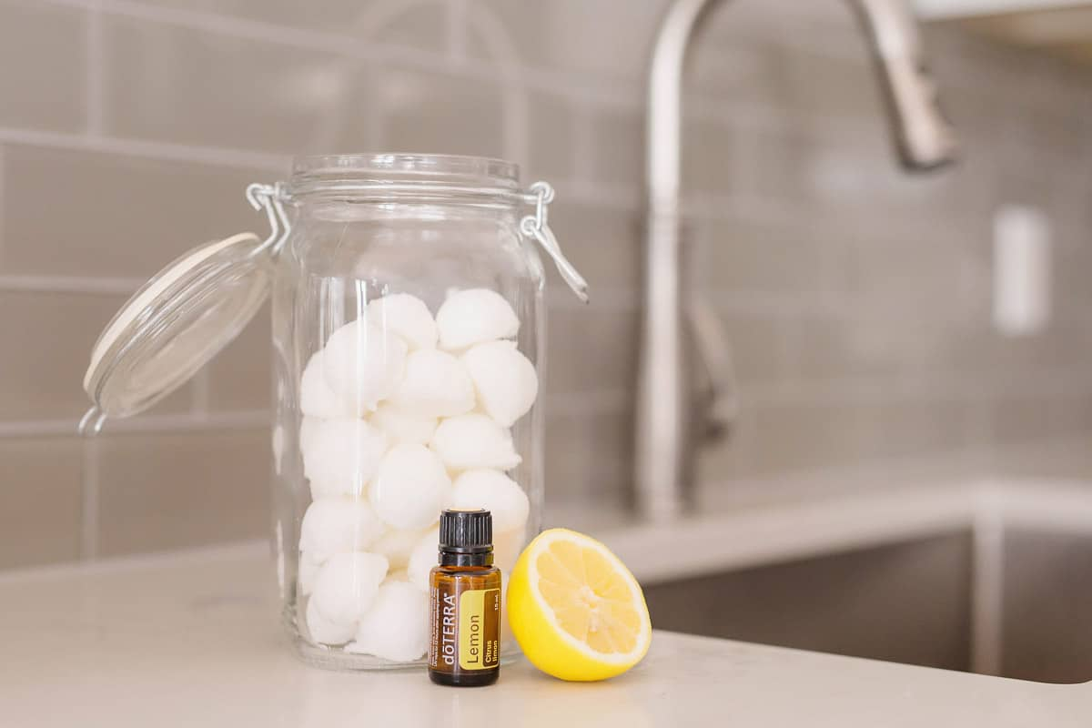 A jar open with white balls with an doterra lemon essential oil with half a slice of lemon in front of it.