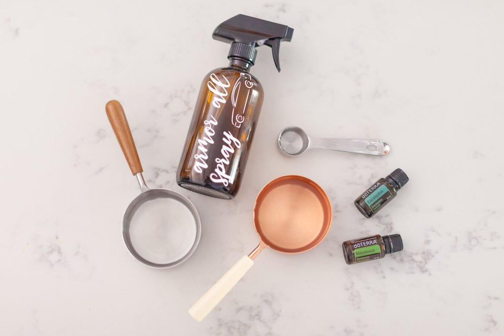 There are five items on a white marble background: a brown spray bottle with the words armor all spray in white writing with an image of a car on the bottle, a copper measuring cup with a white handle, a silver measuring cup with a wooden handle, a silver measuring spoon, a Eucalyptus doterra essential oil bottle and a Melaleuca doterra essential oil bottle.