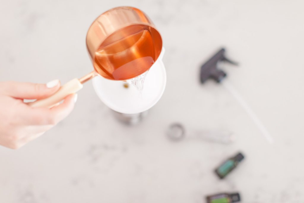 There is a hand holding a copper measuring cup with a white handle pouring clear liquid to a white funnel, a silver measuring spoon, a Eucalyptus doterra essential oil bottle, a Melaleuca doterra essential oil bottle and a spray bottle top.