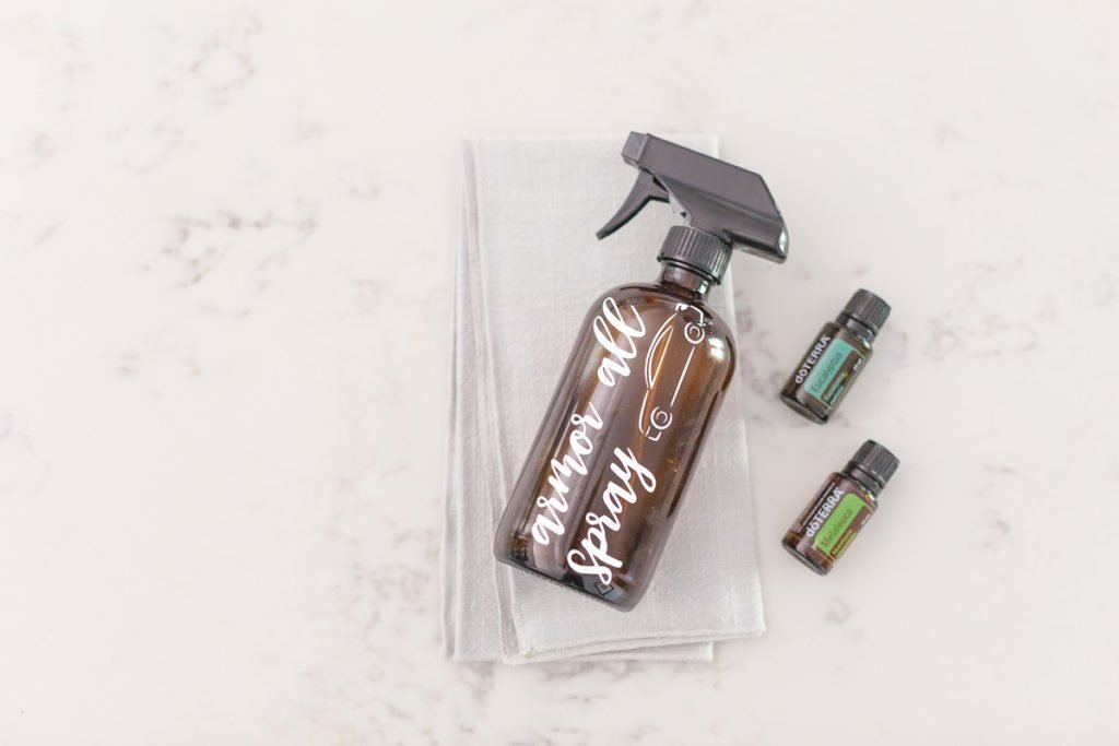 "On a white marble background there is a brown spray bottle with the words ""armor all spray"" in white writing with an image of a car on the bottle on a cloth with a Eucalyptus doterra essential oil bottle and a Melaleuca doterra essential oil bottle on the right side of the bottle."