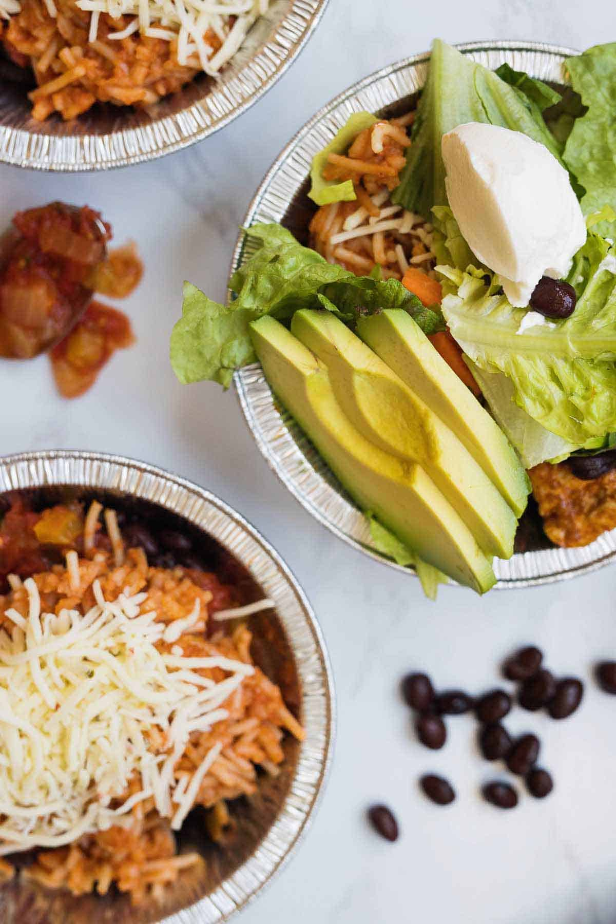 closeup of chicken burrito bowls filled with spanish rice, lettuce and avocado