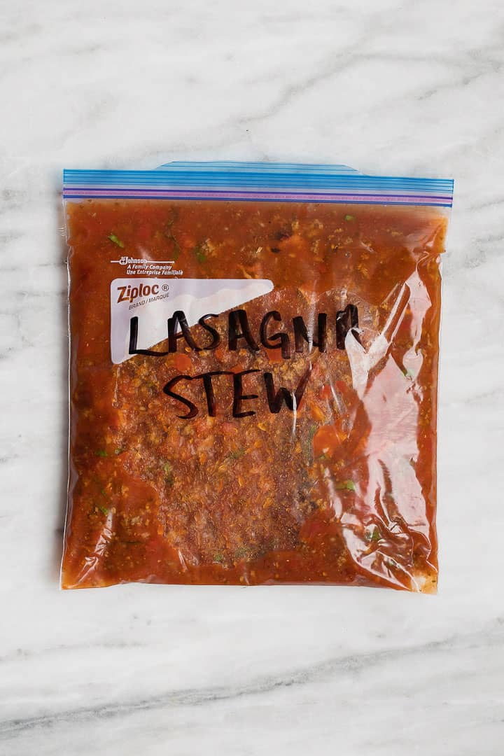 "A ziploc gallon size bag filled with lasagna soup with the words ""Lasagna Stew"" on it."