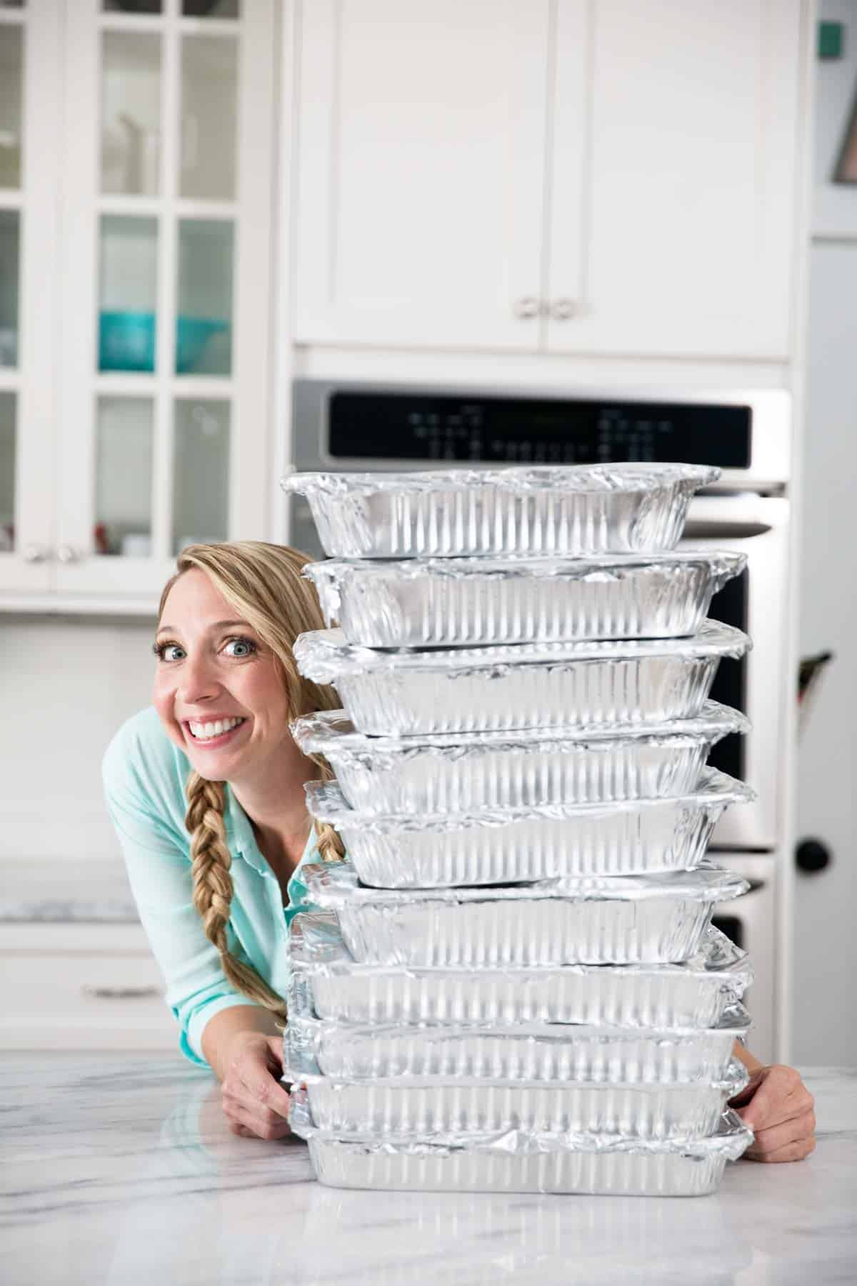 girl with a stack of freezer meals in kitchen