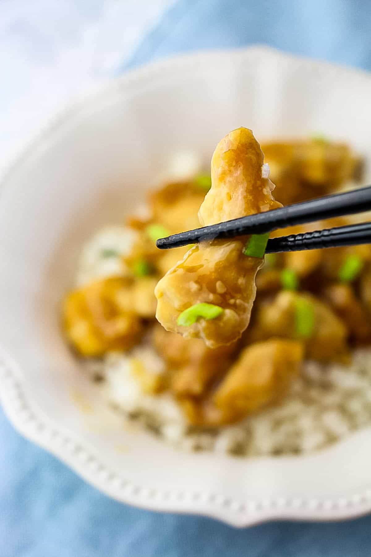 orange chicken with chopsticks
