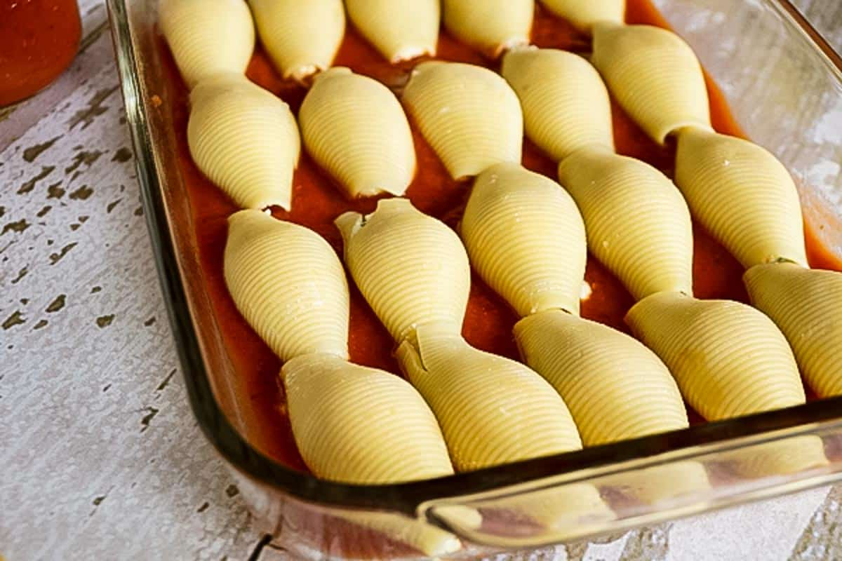 red sauce and cooked jumbo shells in baking dish
