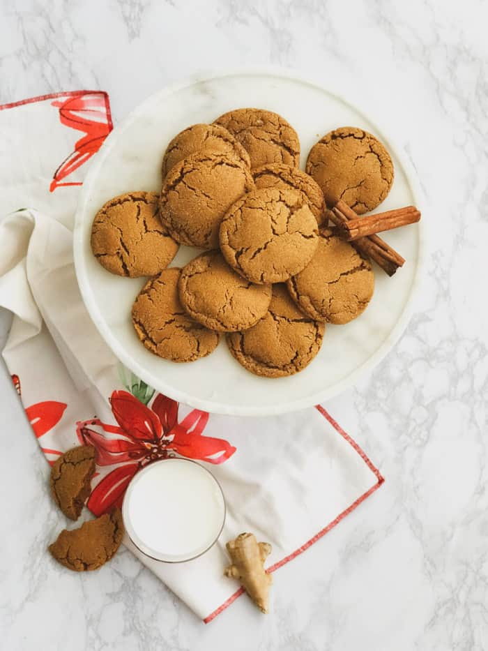 soft delicious chewy ginger molasses cookies on a plate with a glass of milk
