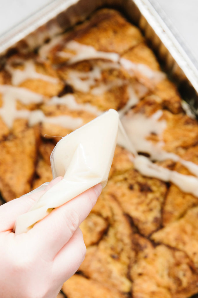 A pan of french toast casserole with a hand pouring out a white bag of icing on it.