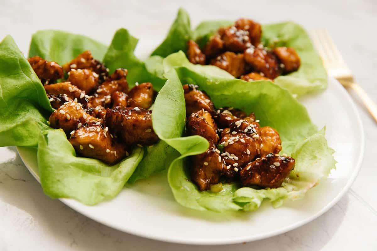A white plate with three lettuce cups with sesame honey chicken in it with a gold fork on the side.
