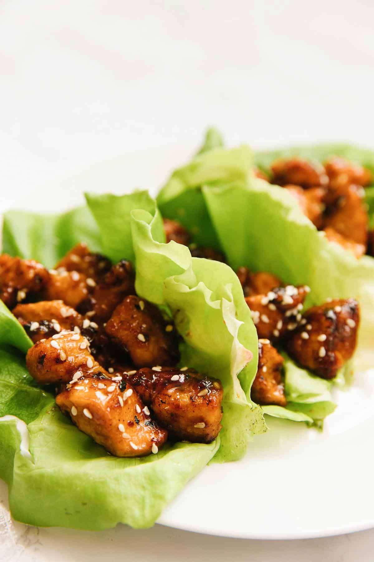 3 lettuce wraps on a white plate on a white marble counter.