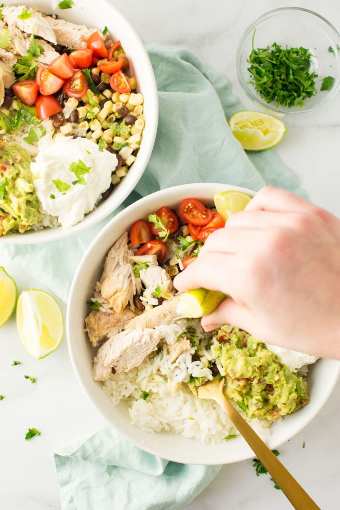 Cilantro Lime chicken in white bowls over white rice and topped with guacamole, sour cream fresh tomatoes and a hand is squeezing fresh lime over bowls.