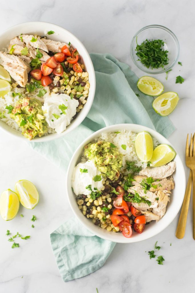Two burrito bowls filled with rice, slow cooker cilantro lime chicken with beans and corn, fresh cherry tomatoes and sour cream. Bowls of fresh chopped cilantro and limes are around it as well.