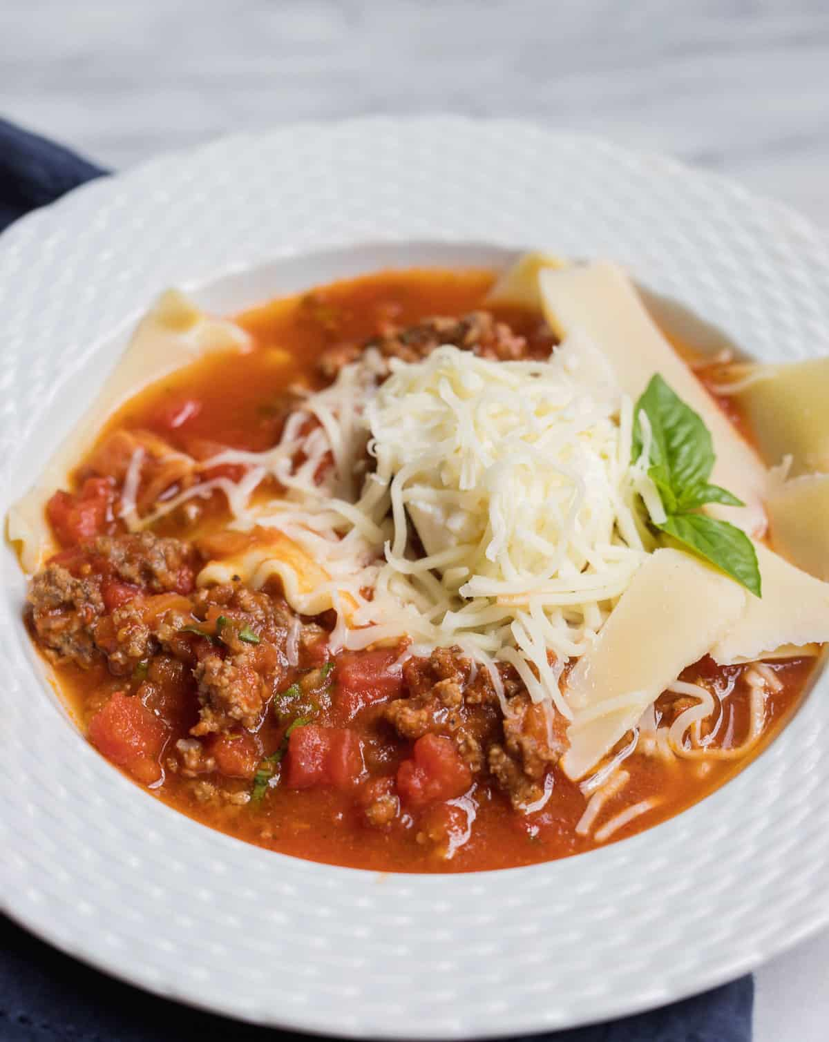A white bowl is lasagna soup topped with cheese and sprig of herbs with a blue napkin underneath.