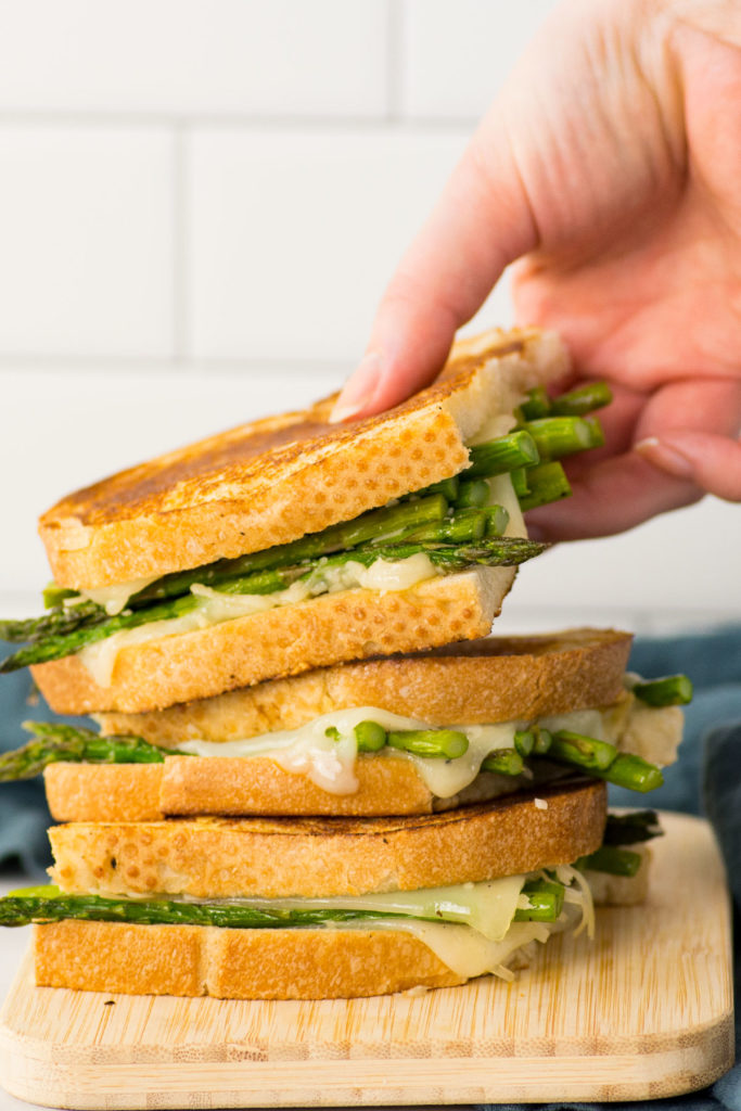 Three asparagus grilled cheese sandwiches piled on a wooden cutting board with a blue napkin behind it. One hand is grabbing the top sandwich.