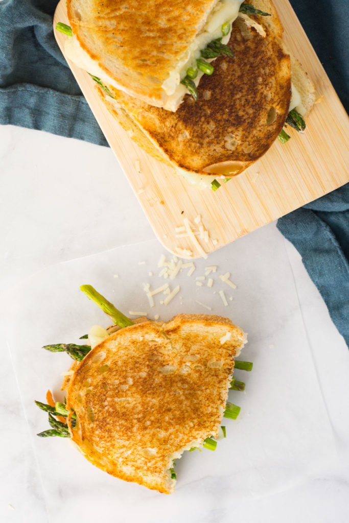 Two asparagus grilled cheese sandwiches on a wooden cutting board with a blue napkin underneath. Another asparagus grilled cheese sandwich is on the counter with a bite taken out with pieces of cheese sprinkled on the counter.
