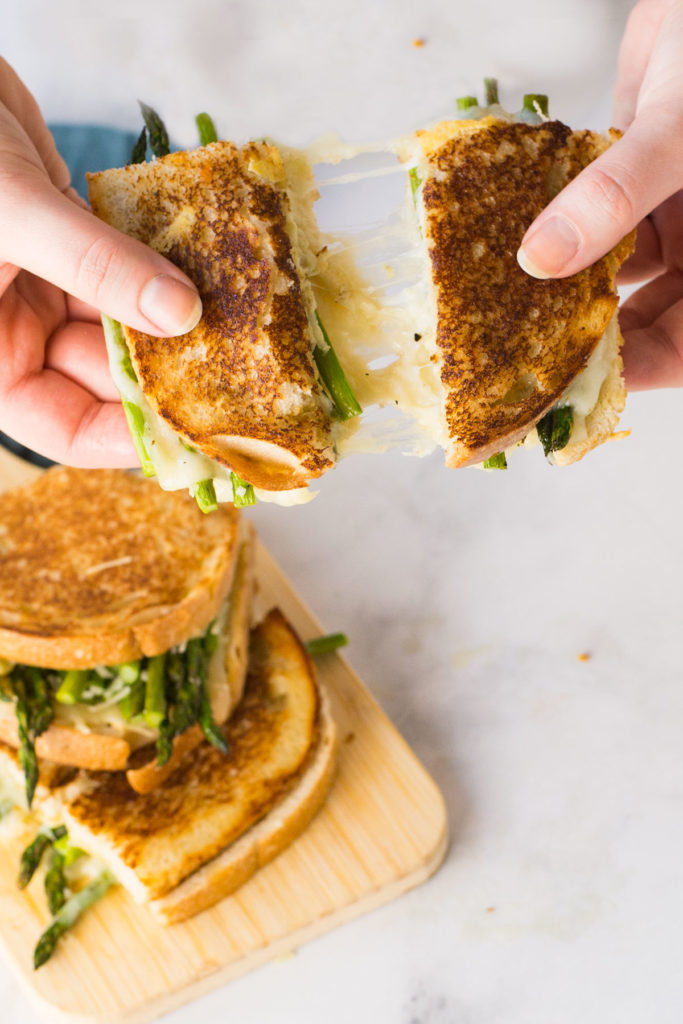 Two asparagus grilled cheese sandwiches on a wooden cutting board with a blue napkin peeking out. Two hands pulling apart a asparagus grilled cheese sandwich in above it.