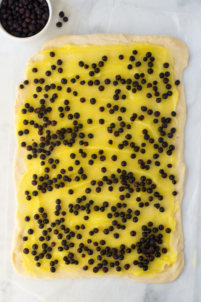 A rectangular piece of rolled out dough with lemon filling and blueberries sprinkled over it. There is a bowl of blueberries in the left corner.