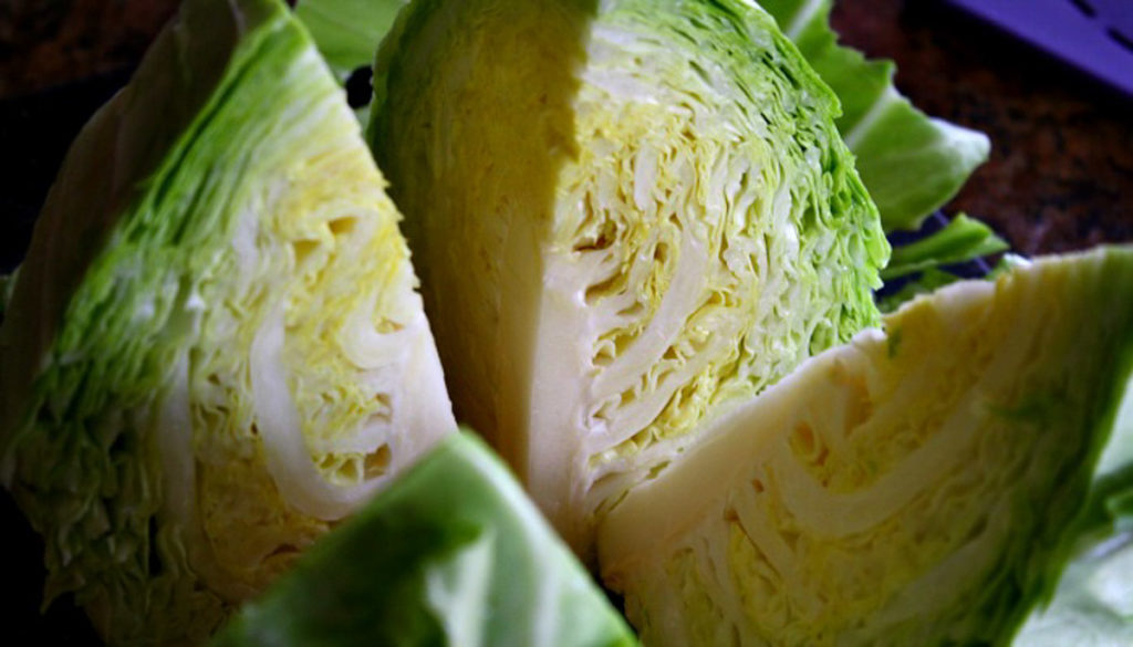 A full head of cabbage sliced in fours and ready to be added to the recipe.