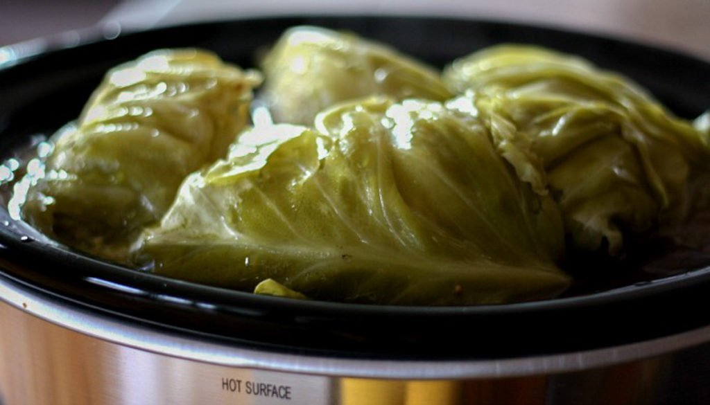 A crock pot filled with steamed cabbage.