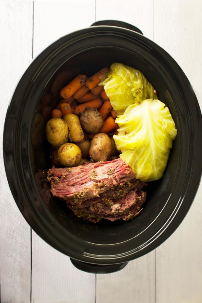 A slow cooker with sliced corned beef with spices. On the side are whole yellow potatoes, whole carrots and pieces of cabbage.