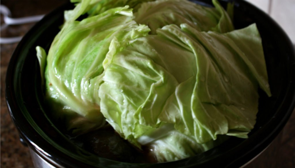 A crock pot filled with cabbage.