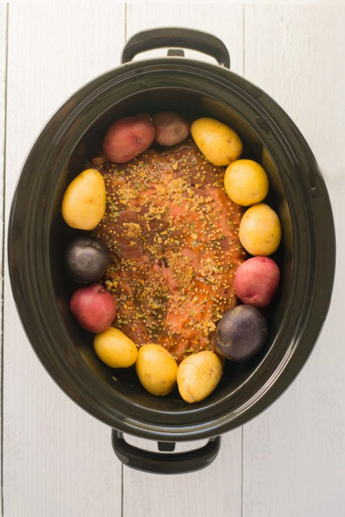 A slow cooker with a corned beef covered in spices and whole small red, purple and yellow potatoes surround it.