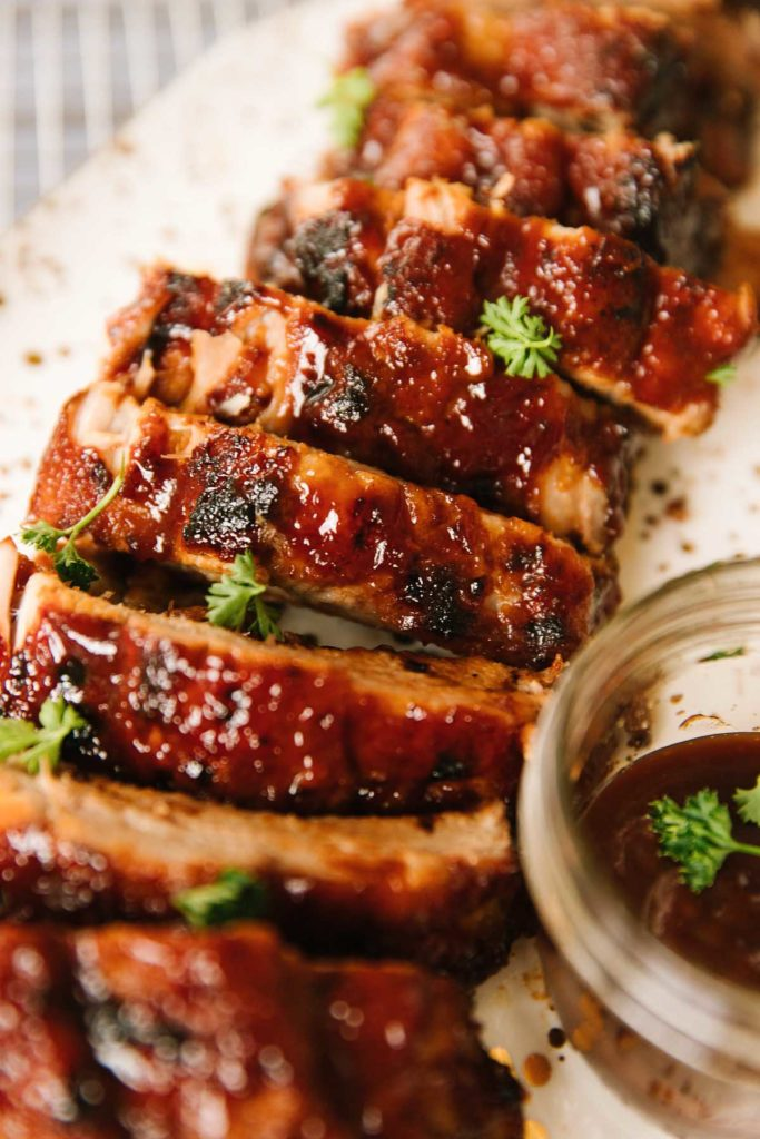 Ribs cut apart and laid together in a line smothered in bbq sauce sprinkled with herbs with a side of bbq sauce in a glass bowl on the right side.