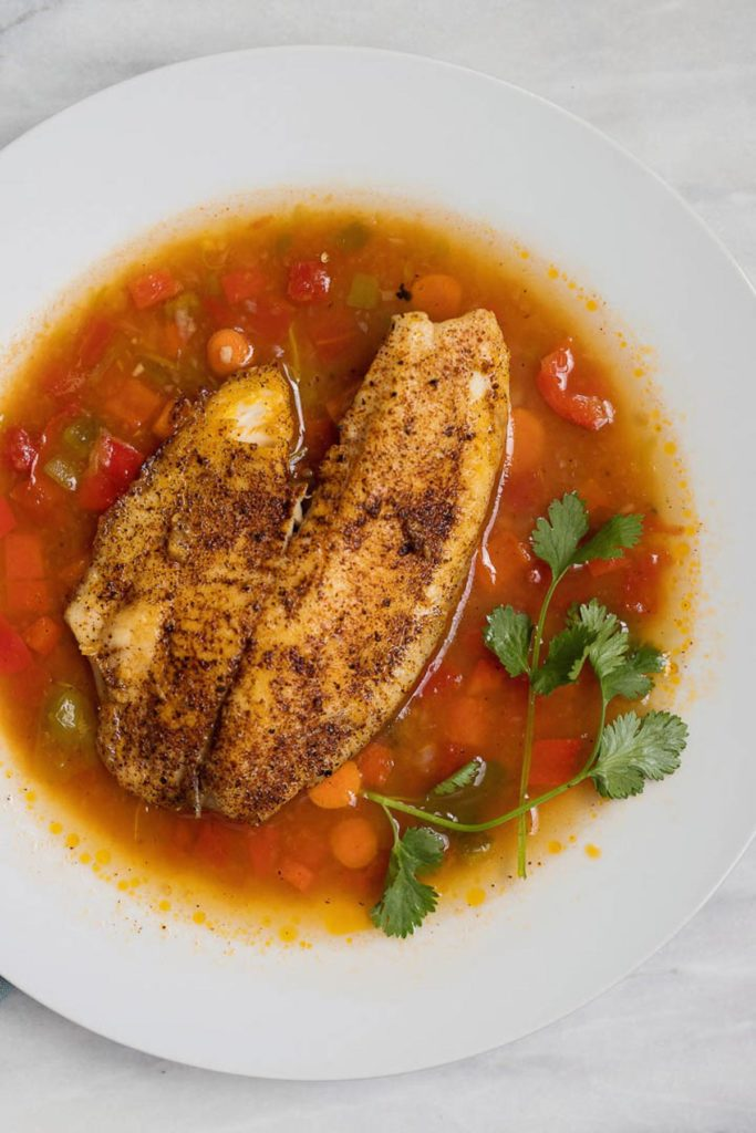 Overhead shot of Moqueca brazilian fish soup recipe with tilapia, carrots, tomatoes and cilantro in a white bowl.