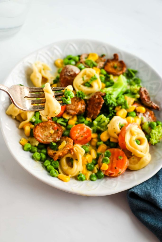 There is a white decorative bowl with pieces of chicken sausage, tortellini, corn, peas, broccoli, carrots. Above the bowl is a fork with tortellini and a small piece of broccoli. Underneath the bowl is a blue denim napkin under the right lower side of the bowl.