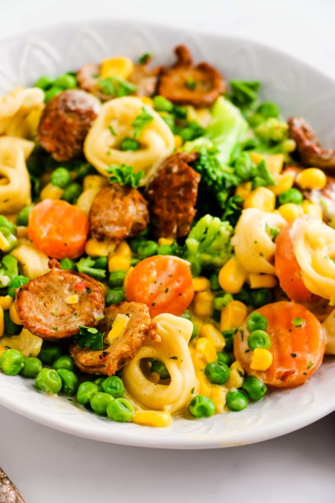 There is a white decorative bowl with pieces of chicken sausage, tortellini, corn, peas, broccoli, carrots. The bottom of the left side is a little piece of a the metal fork.