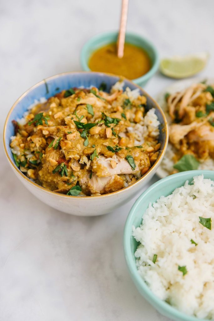 There are three bowls in this picture.  The first bowl has peanut chicken satay with green onions on it. The other bowl has rice with green onions on it  The last bowl has a peanut sauce in it with a spoon sitting in it. There is a plate in the back right corner with chicken satay with rice blurred in the background. There is one slice of lime by the peanut sauce.