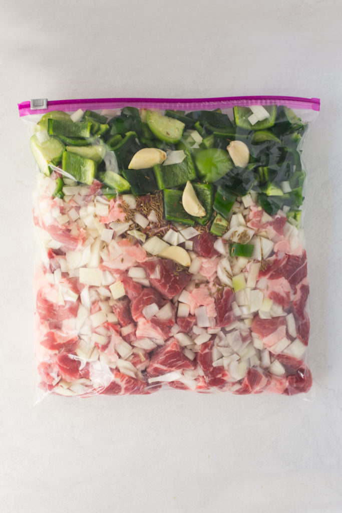 A gallon-size ziploc bag filled with veggies, pork and seasonings.