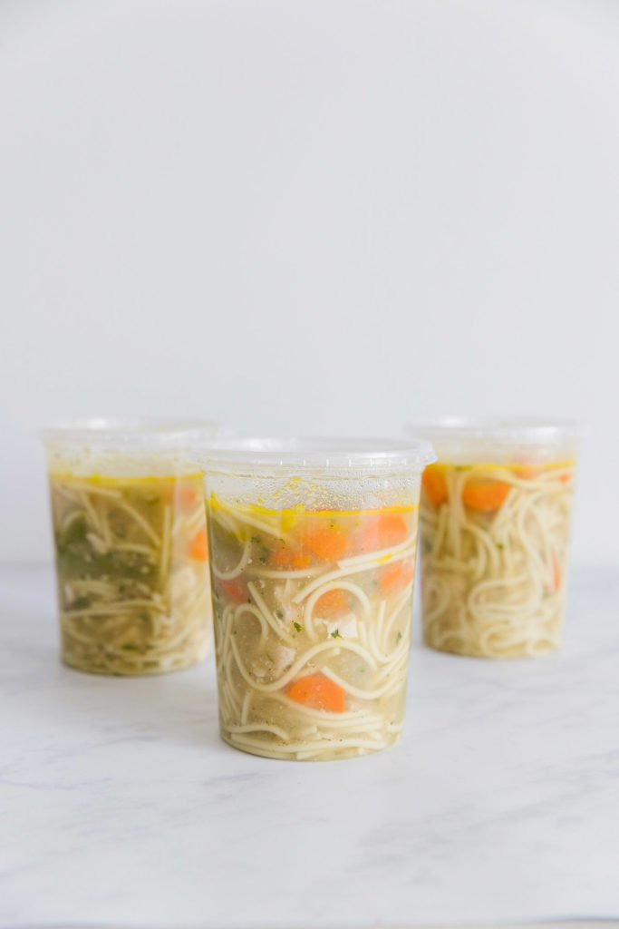 Three clear plastic containers filled with chicken noodle soup.