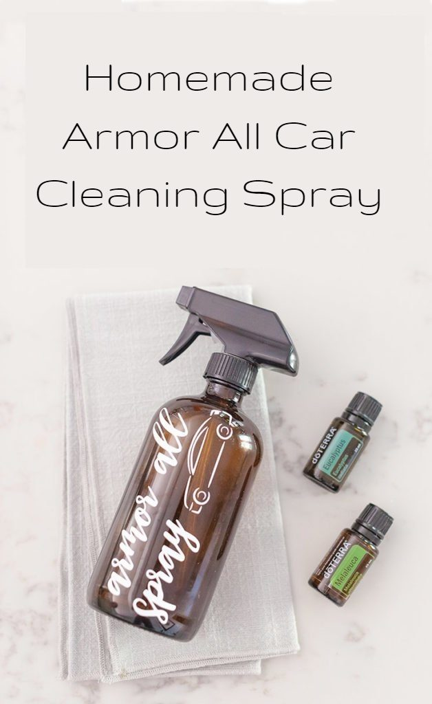 "The words ""Homemade Armor All Car Cleaning Spray"" are at the top of the image. There is a brown spray bottle with the words armor all spray in white writing with an image of a car on the bottle. It is laying on a cloth and there are two doterra essential oil bottles next to it which are Eucalyptus and Melaleuca."