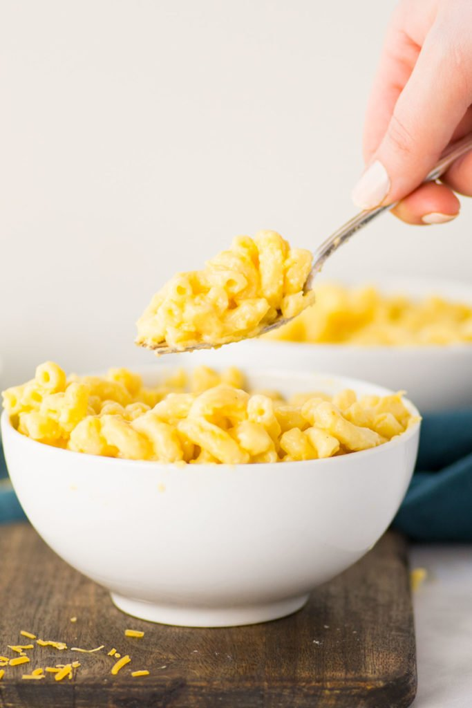 A white bowl full of macaroni and cheese on top of a wooden board with a hand holding a spoon with mac and cheese above the bowl with one other white bowls in the background.