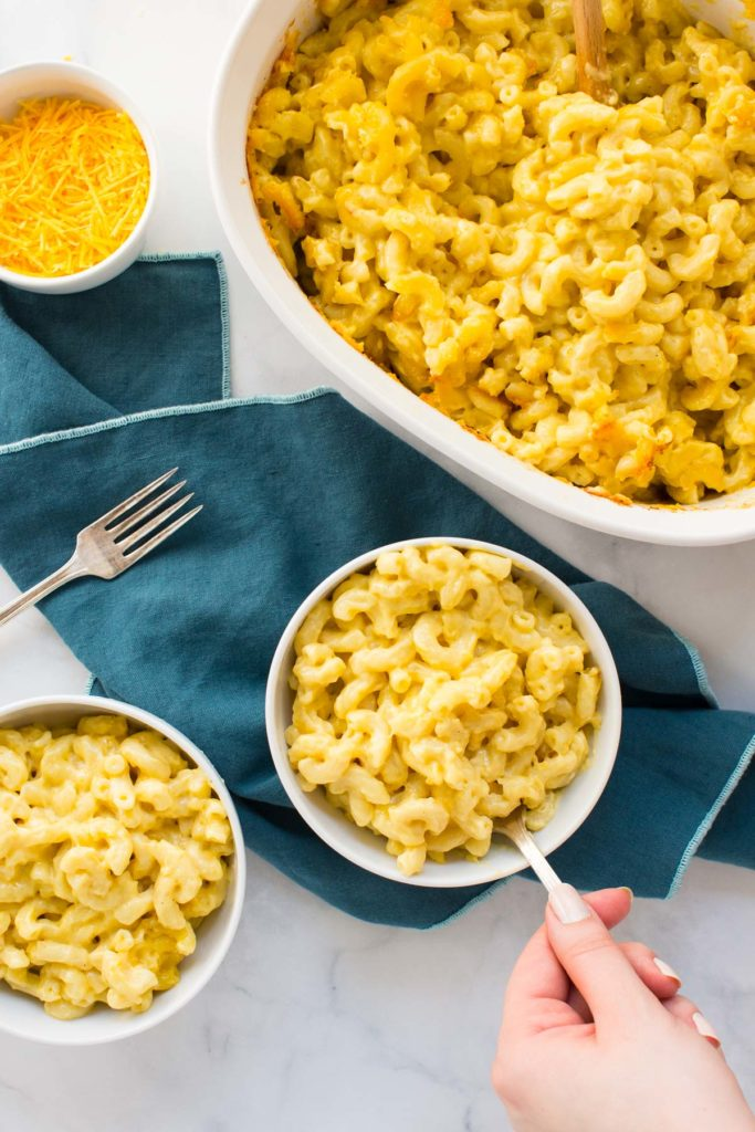 Two white bowls full of macaroni and cheese - one bowl has a fork in it with a hand holding it - on top of a blue napkin with a fork on the side with two other white dishes with cheese in one and a big dish of mac and cheese in the back.