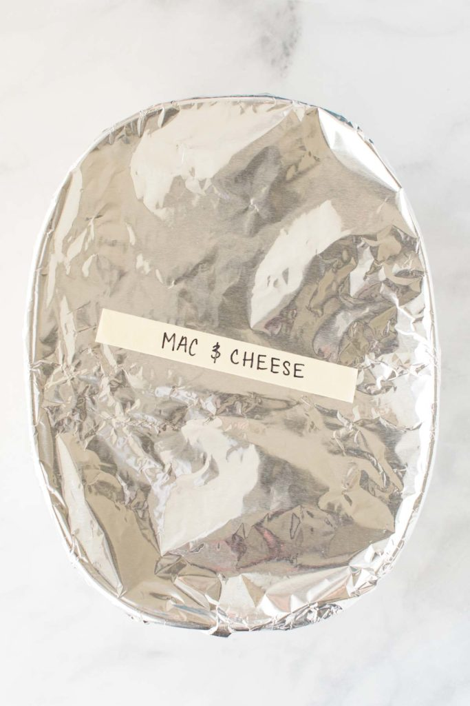 "A oval dish covered in foil with the words ""Mac & Cheese"" written on it."