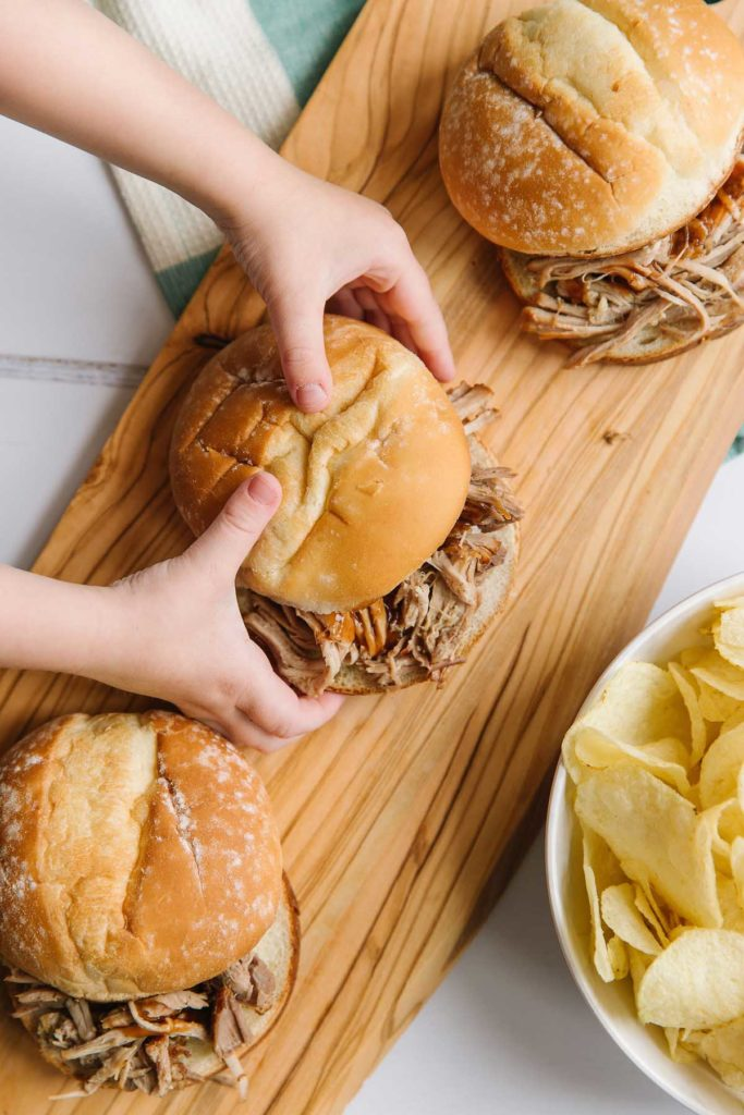 There are two hands holding one pork slider on a wooden plank with two other sliders also on the plank.  There is a white bowl of chips in the right corner and dishtowel of green and white peeking out at the top.