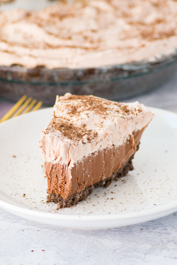 There is one slice of ice cream pie with chocolate crust on a white plate with a gold fork on the side. The rest of the pie is in the back.