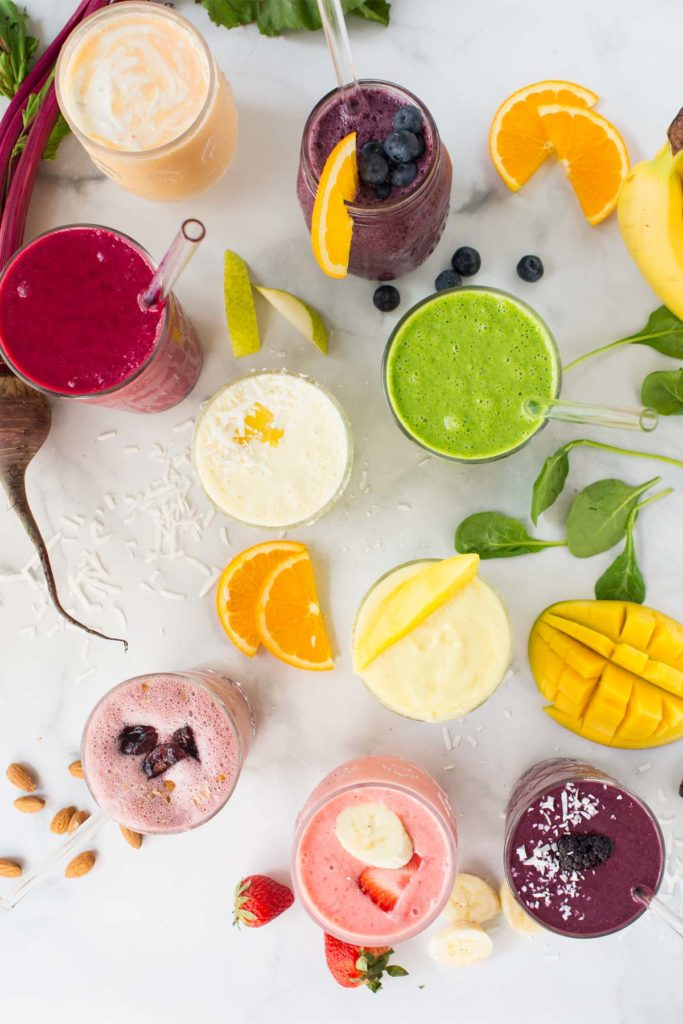9 different smoothie recipes in clear glasses with fruit, spinach and nuts scattered around the glasses.