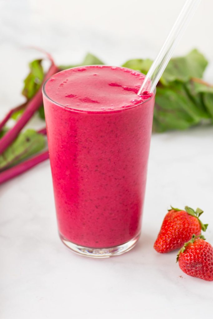 A red smoothie with a straw in a clear glass with strawberries and a beet on the side.