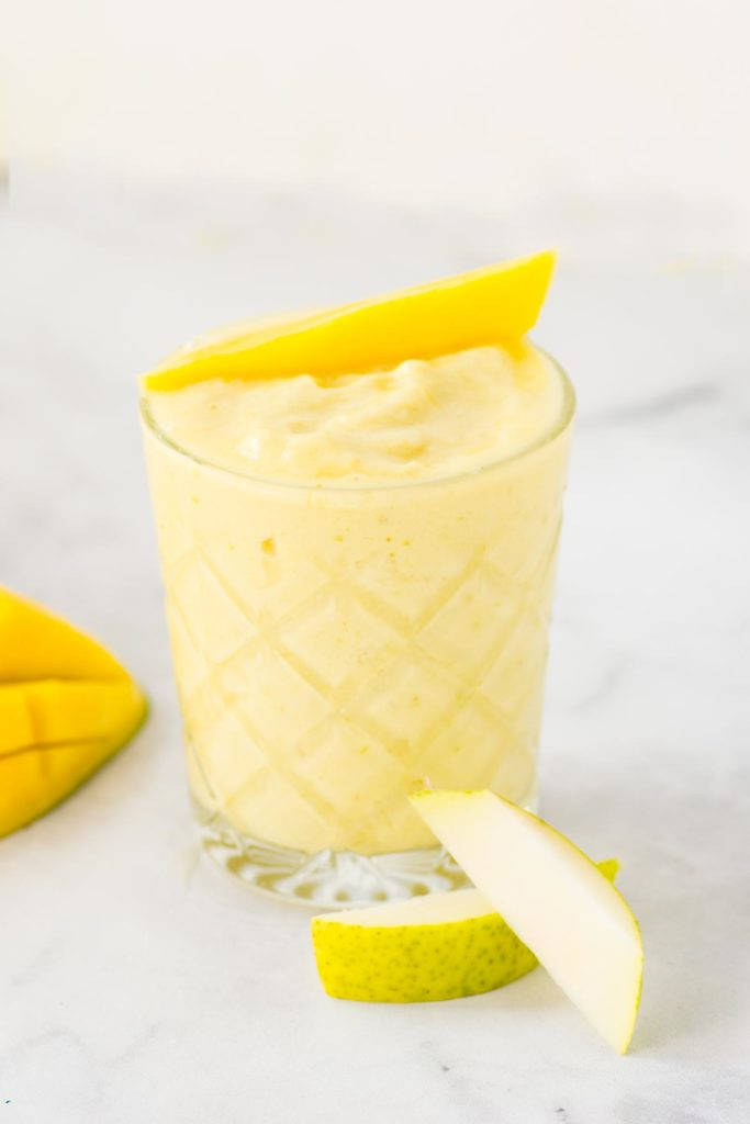 A yellow smoothie in a clear glass with a slices of pear and mango on the side.