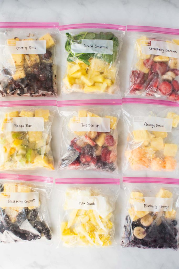 9 clear zippered bags closed, laid flat and filled with make ahead smoothie kits.