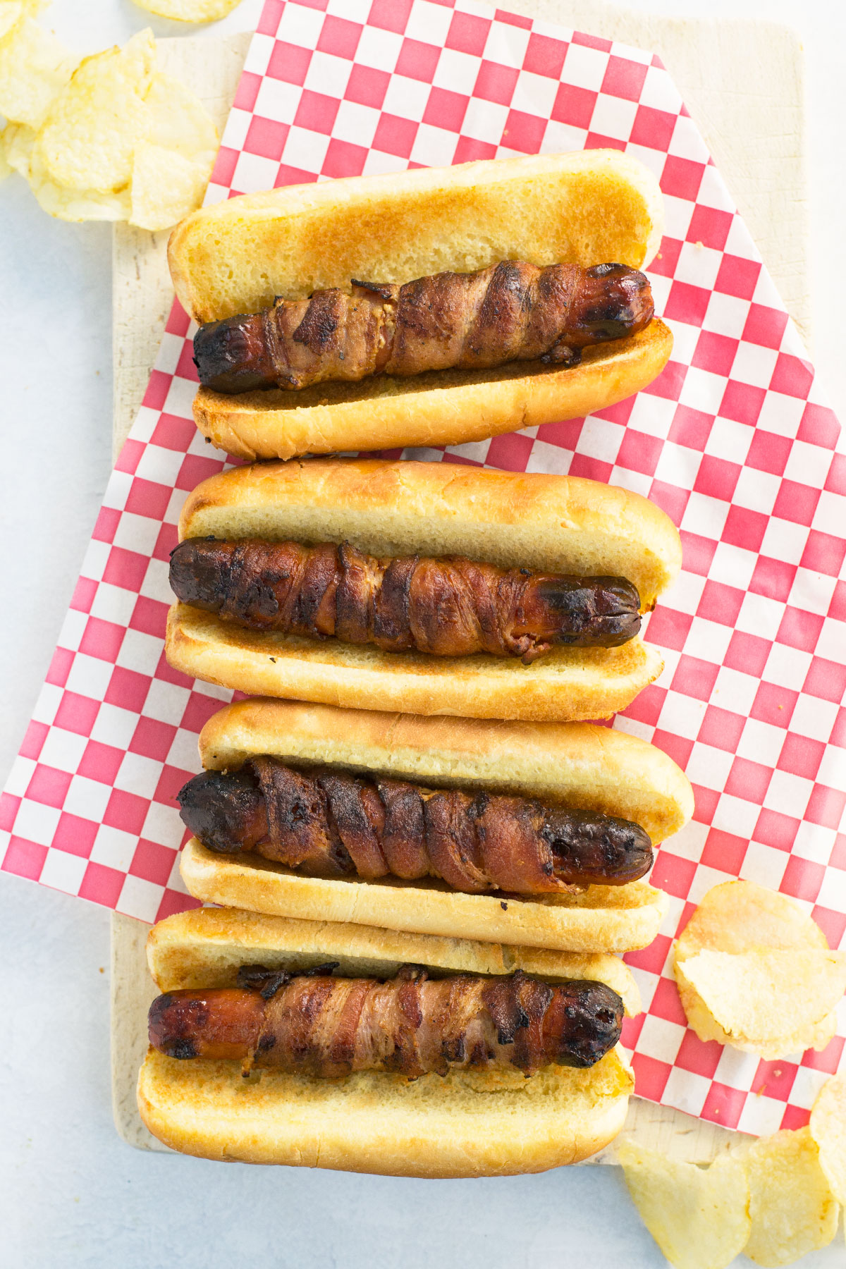 4 hot dogs in buns wrapped in bacon sit atop a red and white checked paper with potato chips around it.